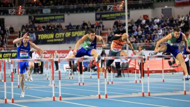 Podczas zawodów lekkoatletycznych odbywa się bieg przez płotki - widać zawodników w trakcie skoku, w tle trybuny pełne kibiców