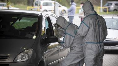 Dwóch medyków w kombinezonach pochyba się nad otwartym oknem samochodu osobowego, aby pobrać wymaz