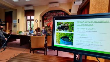 Na zdjęciu: trwa konferencja prasowa, widać prezydenta Michała Zaleskiego i dziennikarzy, na pierwszym planie monitor z danymi dotyczącymi dotacji na małą retencję