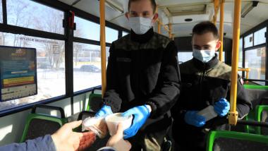 Wolontariusze w maseczkach i rękawiczkach wręczają pojemniki z posiłkiem osobie potrzebującej