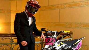 Zawodnik Pit Bike w smokingu i kasu stoi przy swoim pojeździe