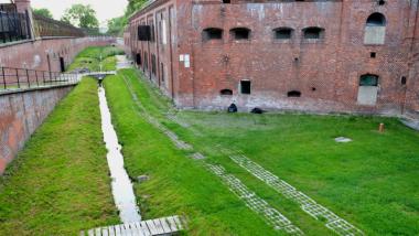 Na zdjęciu widać fort IV i okalającą go fosę, w której rośnie trawa