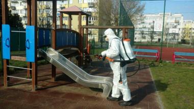 Pracownik ubrany w kombinezon ochronny przeprowadza dezynfekcję zjeżdżalni na placu zabaw