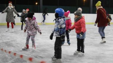 Dzieci na łyżwach leżdżą po lodowisku
