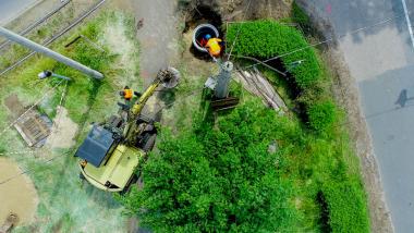 Na zdjęciu pracownicy w kamizelkach wchodzą do studni