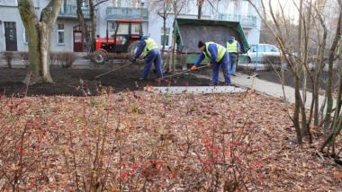 Między blokami nasadzono małe krzewy, w tle widać osoby pracujące przy powstaniu skweru