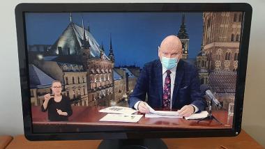 ekran z widocznym prezydentem Zaleskim podczas konferencji prasowej oraz tłumaczka języka migowego