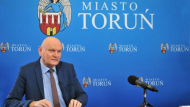 Prezydent Michał Zaleski na tle niebieskiej ścianki promocyjnej z herbem Torunia