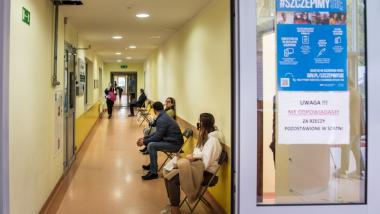 Na zdjęciu osoby czekają na korytarzu na szczepienie