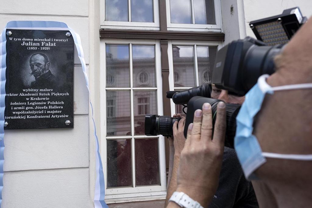 Na zdjęciu: tablica poświęcona Julianowi Fałatowi i obiektyw kamery