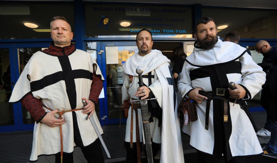 mężczyźni w strojach krzyżackich witają gości przy wejściu