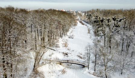 Widok z drona na ośnieżony Park Miejski i mostek na Martówce
