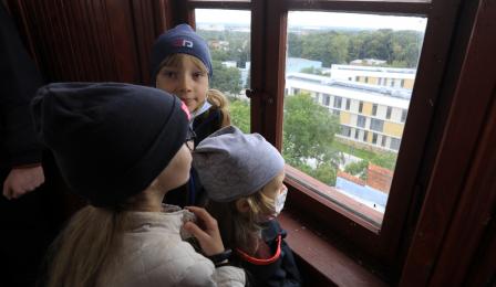 Na zdjęciu: troje dzieci patrzy przez okno w wieży ciśnień