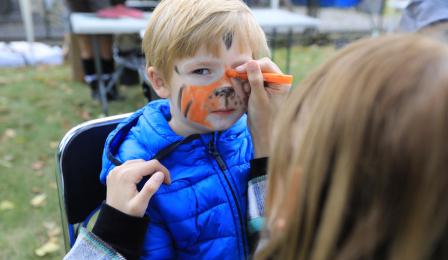 Na zdjęciu: podczas pikniku jest malowanie buzi dzieci - chłopiec ma twarz malowaną na pomarańczowo (tygrys)