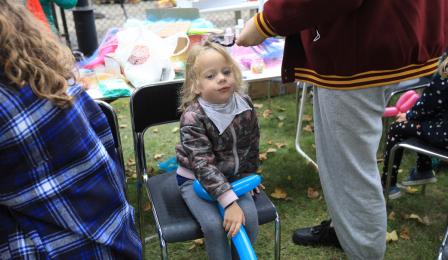 Na zdjęciu: dziewczyna z balonem w dłoni podczas robienia ozdobnych warkoczyków