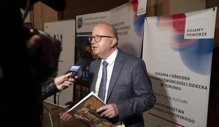 Dyrektor galerii Dariusz Delik udziela wywiadu telewizji