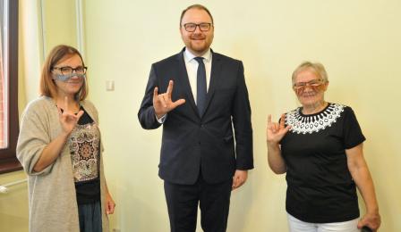 Grażyna Skrzeszewska i tłumaczka Sylwia Fedus uczą wiceprezydenta Torunia Pawła Gulewskiego języka migowego