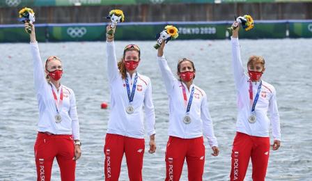 Zawodniczi czwórki podwójnej machają po dekoracji medalowej