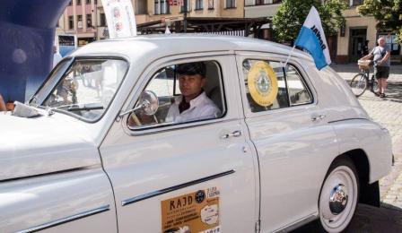 Na zdjęciu: mężczyzna w białym zabytkowym samochodzie
