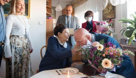 Na zdjęciu prezydent Michał Zaleski wręcza bukiet kwiatów stulatce, Jadwidze Marii Strawińskiej i całuje jej dłoń