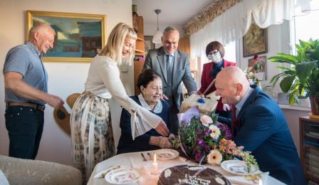 Na zdjęciu prezydent Michał Zaleski wręcza bukiet kwiatów stulatce, Jadwidze Marii Strawińskiej
