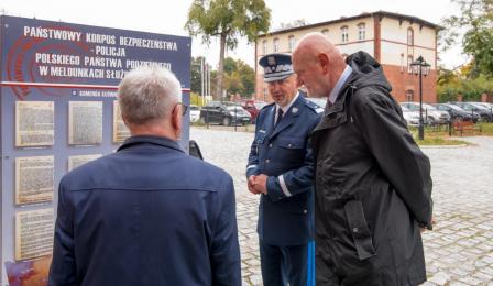 Na zdjęciu: prezydent Michał Zaleski, starosta Marek Olszewski i przedstawiciel policji patrzą na planszę znajdującą się na wystawie poświęconej historii policji