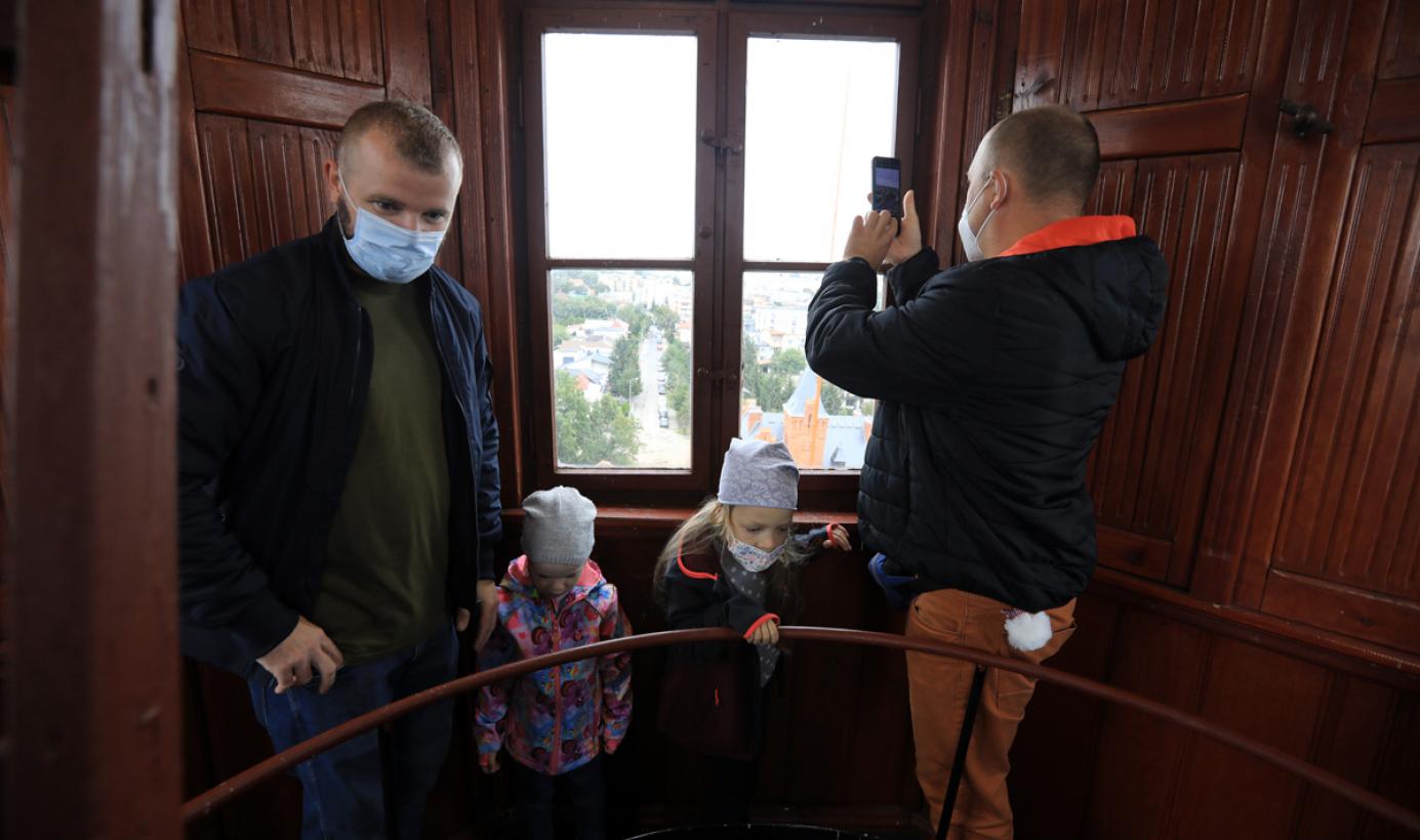 Na zdjęciu dwóch mężczyzn i dwoje dzieci stoją przy oknie w wieży ciśnień, jeden z mężczyzn robi zdjęcie telefonem